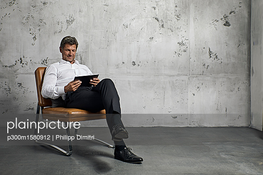 Mature man using digital tablet in front of concrete wall - p300m1580912 by Philipp Dimitri
