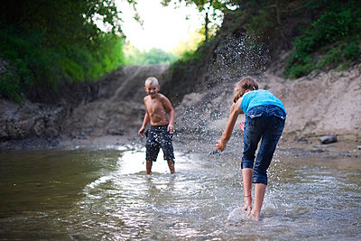 Girl and Boy Playing in River - p1169m1054937 by Tytia Habing