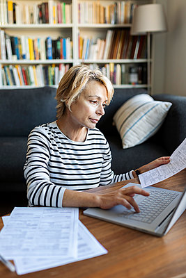 Mature woman with documents using laptop at home - p300m2144949 by Valentina Barreto