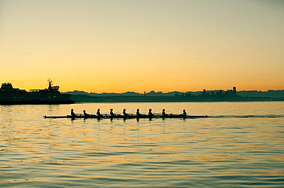 Team rowing boat in bay - p555m1478282 by Pete Saloutos