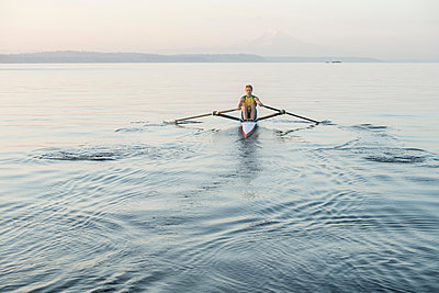 Man rowing row boat in sea around Bainbridge Island, Washington, USA - p924m1174816 by Pete Saloutos