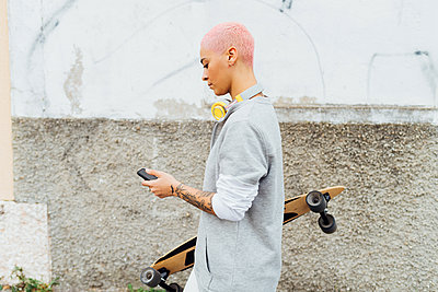 Side view of skateboarder using cellphone - p924m2237517 by Eugenio Marongiu