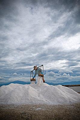 Vietnamese female worker on top of a salt heap, unloads her wicker baskets, Khanh Hoa province, Vietnam, Southeast Asia - p934m1093559f by THIERY BEYNE