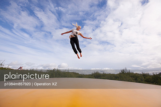 Young woman jumping on trampoline  - p1084m857920 by Operation XZ