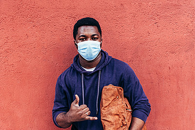 Portrait of an African American boy with face mask on red wall background. - p1166m2254939 by Cavan Images