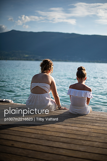 Two girls in white dresses sitting on wooden pier - p1007m2216523 by Tilby Vattard