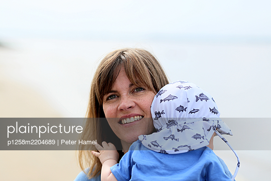 Happy mother carries toddler in her arms - p1258m2204689 by Peter Hamel