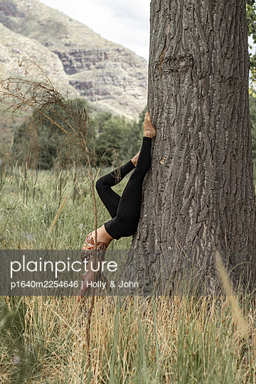 Woman doing handstand leaning against tree - p1640m2254646 by Holly & John