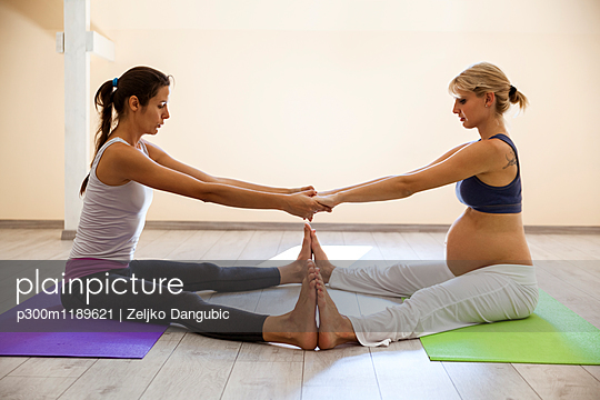 Prenatal yoga, female yoga instructor, stretching legs