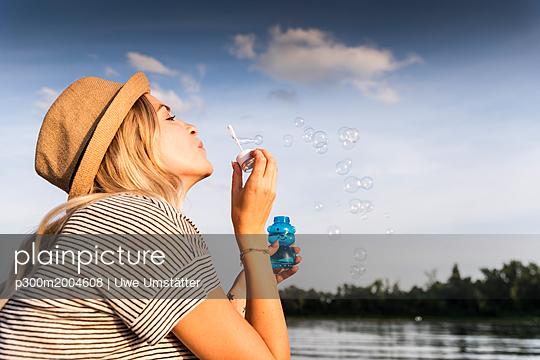 Blond woman blowing soap bubbles - p300m2004608 von Uwe Umstätter