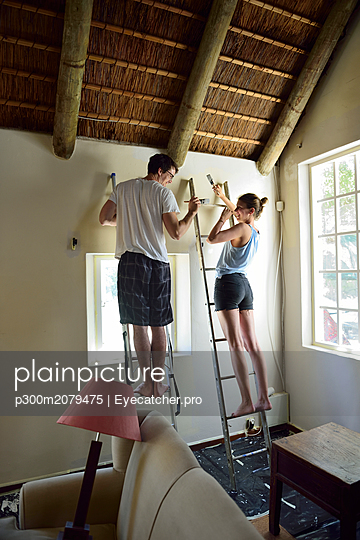 Young couple renovating their home painting the wall together - p300m2079475 by Eyecatcher.pro