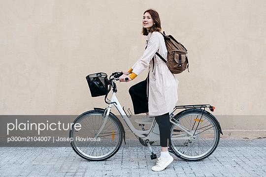 Woman with e-bike at a wall - p300m2104007 by Josep Rovirosa