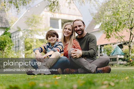 Happy family sitting on grass in their garden - p300m2166722 by Kniel Synnatzschke