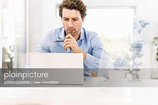 Mid adult man concentrating while working on laptop in office - p300m2226590 by Uwe Umstätter