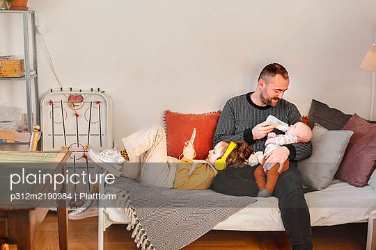 Father with children in living room - p312m2190984 by Plattform