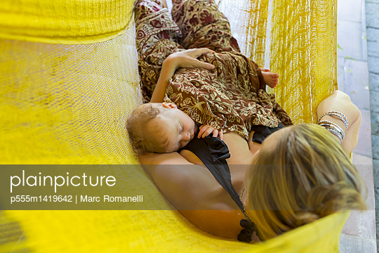 Caucasian mother and baby relaxing in hammock