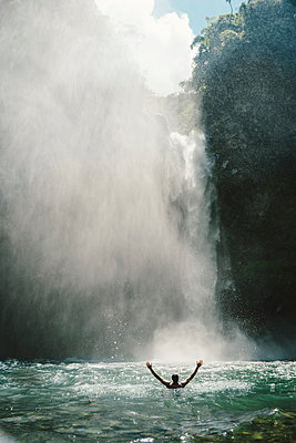 Rear view of man with arms outstretched in river by majestic waterfall - p1166m1145145 by Cavan Images