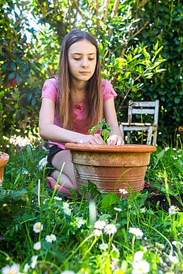 Portrait of girl potting tomato plant in a garden - p300m2199481 by Sandra Roesch