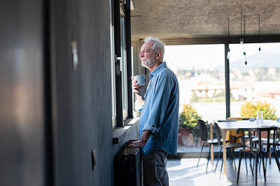 Man with coffee cup looking through window while standing at home - p300m2265918 by Emma Innocenti