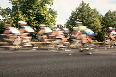 Large group of male cyclists speeding on urban road in racing cycle race - p429m1118411f by Seb Oliver