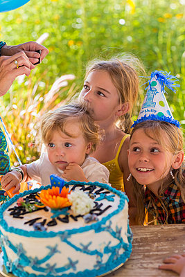 Family celebrating birthday together outdoors - p555m1421233 by Marc Romanelli