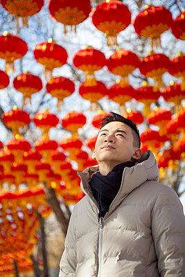 Asiatischer Mann betrachtet Lampions - p817m2159100 von Daniel K Schweitzer
