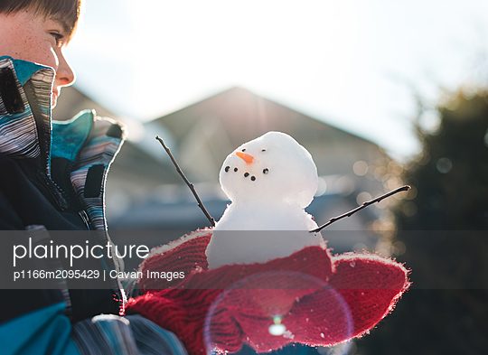 Young boy wearing red wool mittens holding a small snowman in the sun. - p1166m2095429 by Cavan Images