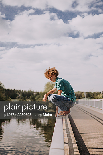Young man on bridge railing, portrait - p1267m2259695 by Jörg Meier