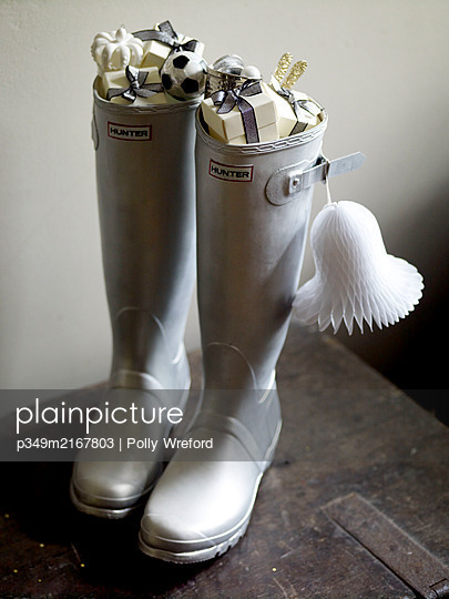 Pair of silver wellington boots filled with presents - p349m2167803 by Polly Wreford