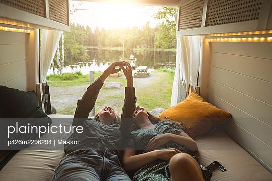 Female Friends taking selfie through smart phone in camping van - p426m2296294 by Maskot