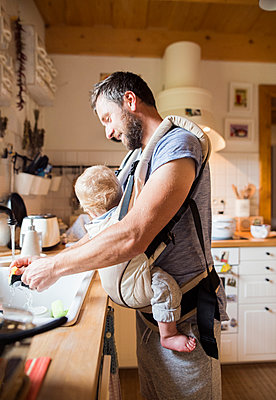 Happy father with baby in baby carrier doing the dishes - p300m1205331 by HalfPoint