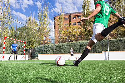 Football player shooting the ball on football field - p300m2083022 by Andrés Benitez