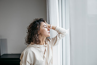 Portrait of pensive woman looking out of window - p300m2160595 von Katharina Mikhrin