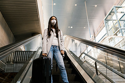 Woman wearing face mask while standing with luggage on escalator at subway station - p300m2240315 by Ezequiel Giménez
