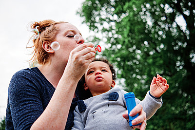 Mother blowing bubbles with son at park - p300m2287381 by Angel Santana Garcia