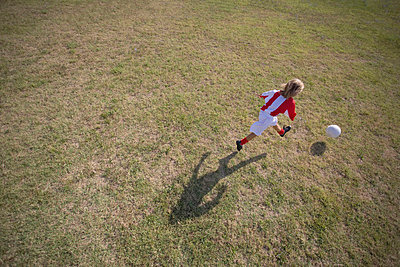 Footballer kicking soccer ball - p3071211f by Enrico  Calderoni