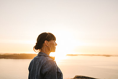 Woman looking at sunset over sea - p312m2217108 by Stina Gränfors