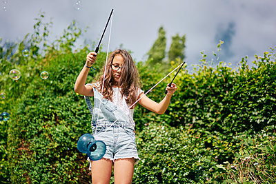Girl playing with diabolo in garden - p429m2145798 by GS Visuals