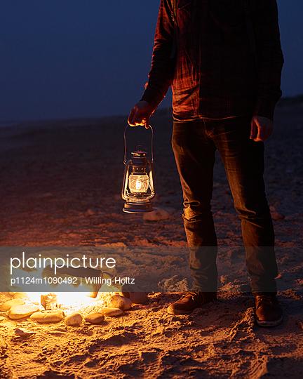 Mann mit Laterne am Lagerfeuer - p1124m1090492 von Willing-Holtz