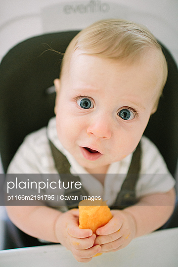 Baby making a funny expression as he tries a new food - p1166m2191795 by Cavan Images