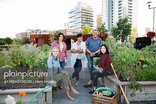 Portrait happy mature friends in urban community garden - p1192m2130122 by Hero Images
