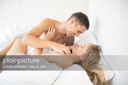 Couple in love embracing in bed - p1640m2259583 by Holly & John