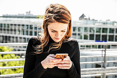 Woman text messaging on roof terrace - p300m2004800 von Jo Kirchherr