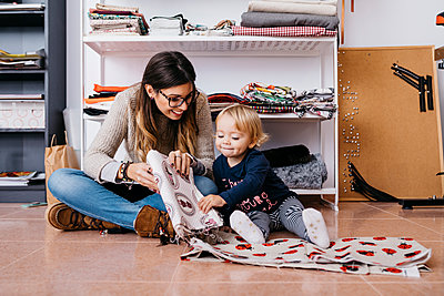Mother and little daughter sitting on the floor at home checking fabrics - p300m2059009 by Josep Rovirosa