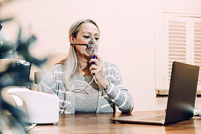Senior woman taking online cosultation while inhaling through nebulizer at home - p300m2240414 by Eloisa Ramos