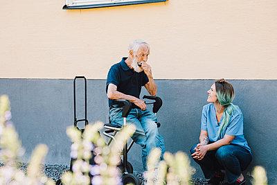 Smiling female nurse looking at senior man playing harmonica against wall at back yard - p426m2074380 by Maskot