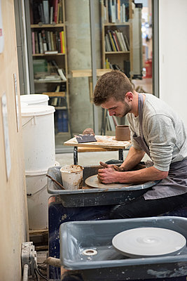 Man in art studio using pottery wheel - p429m1513868 by G. Mazzarini