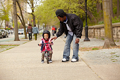 Father helping daughter ride bicycle on sidewalk - p555m1479784 by Granger Wootz