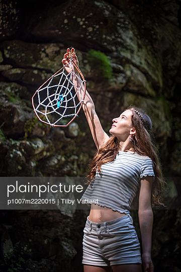 Teenage girl holding up a dreamcatcher - p1007m2220015 by Tilby Vattard