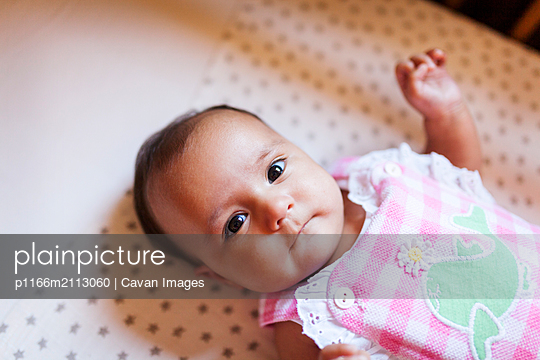 High angle portrait of cute baby girl lying on bed at home - p1166m2113060 by Cavan Images